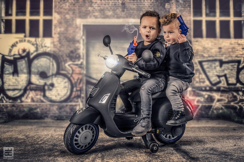 Twee jongetjes op een speelgoed scooter met nerf guns. Studiofotografie en Photoshop