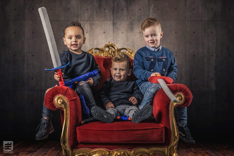 3 jongens als stoere ridders met schuimrubber zwaarden zitten op een rode koningsstoel. studio fotografie en Photoshop Composite