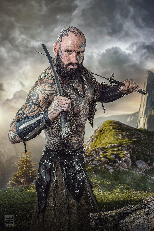 Volledig getatoeëerde gespierde man met twee zwaarden klaar voor het gevecht met bergen op de achtergrond. Studio fotografie en Photoshop.