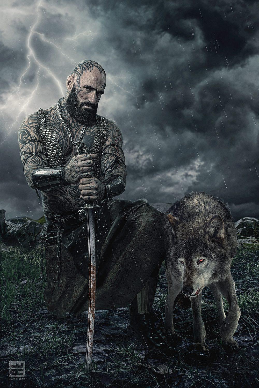 Volledig getatoeëerde gespierde man met een zwaard in de regen na een gevecht. Naast hem zijn trouwe wolf. Studio fotografie en Photoshop.